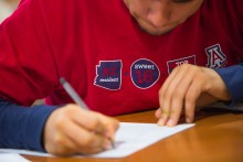Picture of UA student writing on a piece of paper